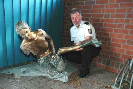 Jochen Haase von der Wasserschutzpolizeistation Travemünde zeigt die beschädigte Nymphe. Die Skulptur vom Priwall-Strand wurde heute nacht umgefahren. Foto: <b>TA</b>